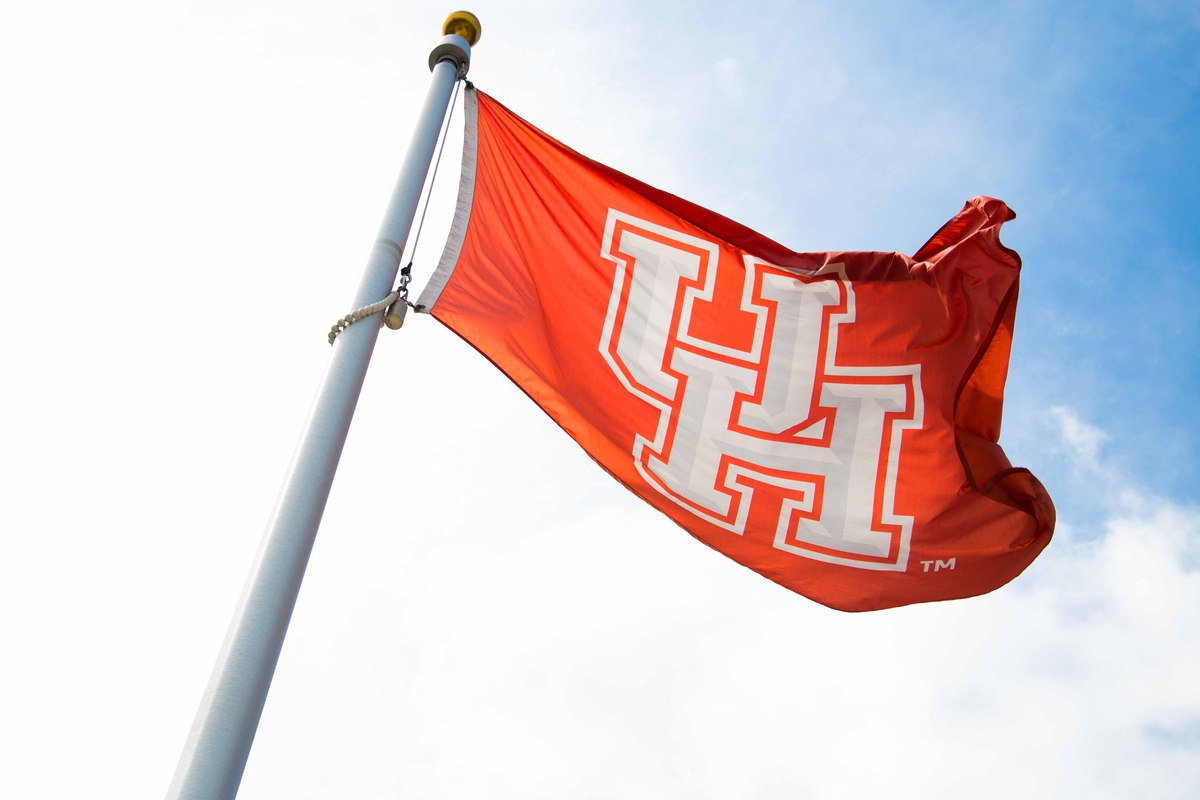 Red flag flying with white UH logo against a clear blue sky.