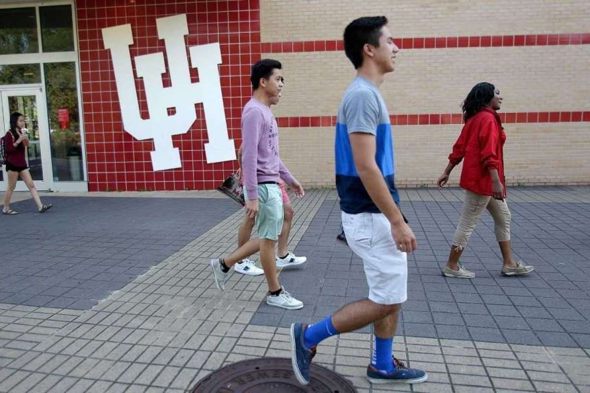Five college students walking on the University of Houston's campus.